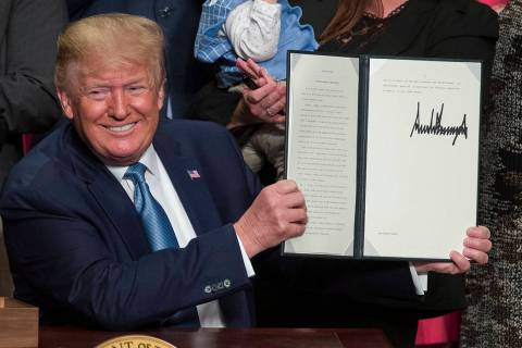 President Donald Trump holds up a signed executive order at the Ronald Reagan Building and Inte ...