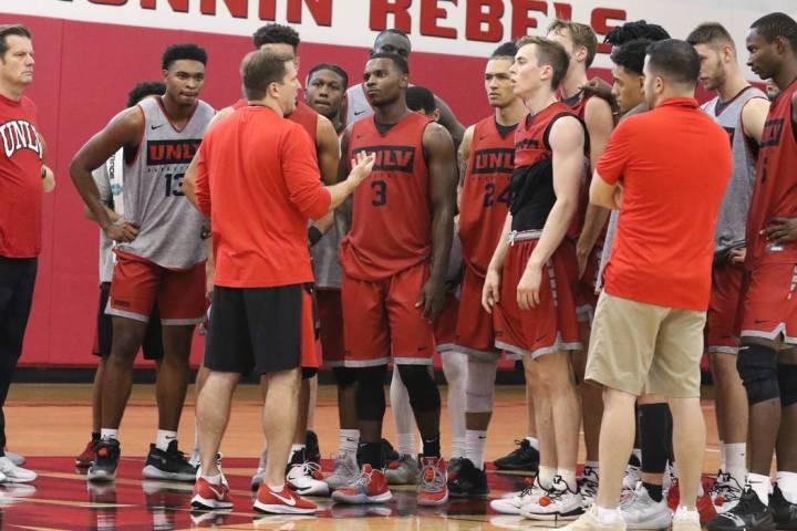 UNLV Rebels head coach T.J. Otzelberger, center, talks to his players after team's first basket ...