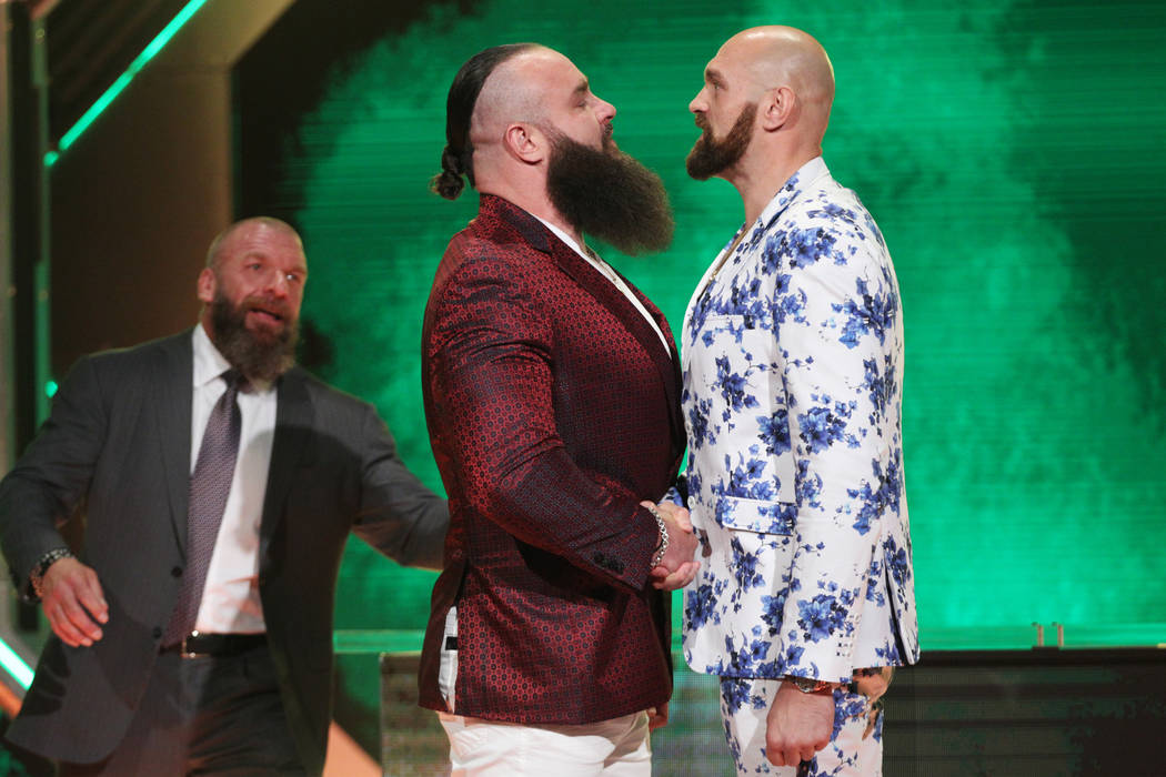 Paul Levesque, left, better known as Triple H, looks on as Braun Strowman, center, and Tyson Fu ...