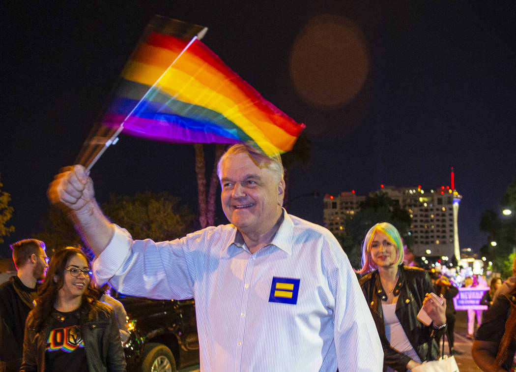 Governor Steve Sisolak waves a flag while marching in the Pride parade on Friday, Oct. 11, 2019 ...