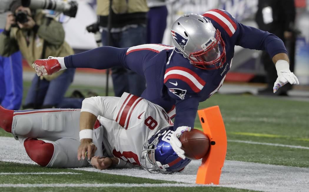 New England Patriots linebacker Kyle Van Noy dives over New York Giants quarterback Daniel Jone ...