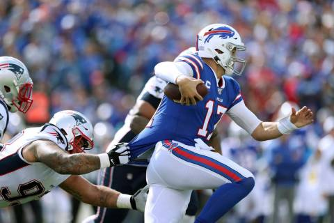 Buffalo Bills quarterback Josh Allen tries to break free from the grasp of of New England Patri ...