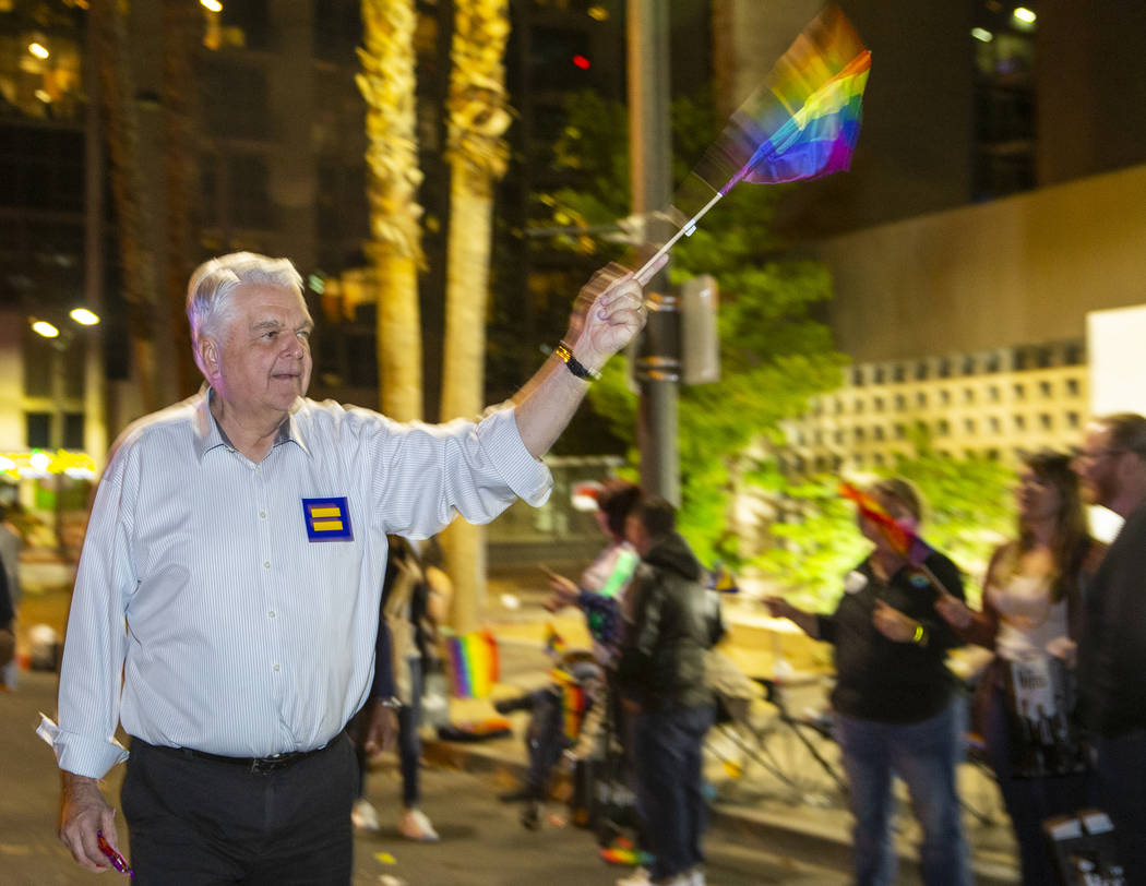 Gov. Steve Sisolak waves a flag while marching in the Pride parade on Friday, Oct. 11, 2019 in ...