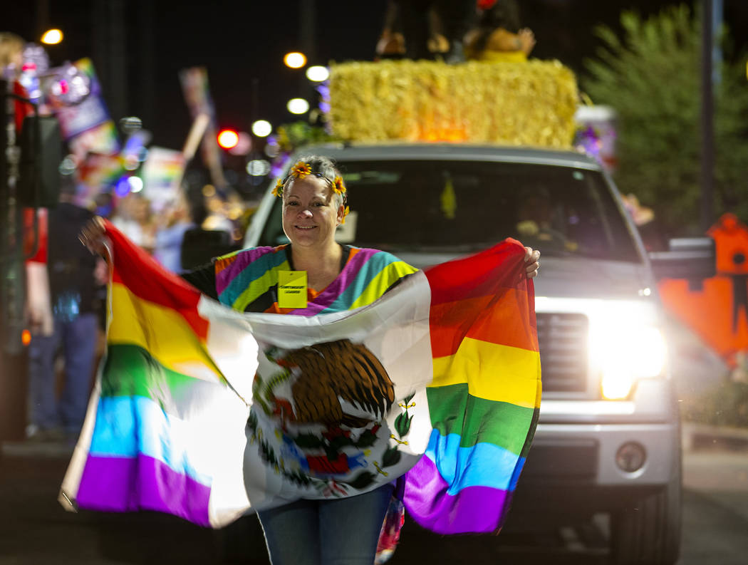 A participant carries a flag while leading her float during the annual Las Vegas Pride Night Pa ...