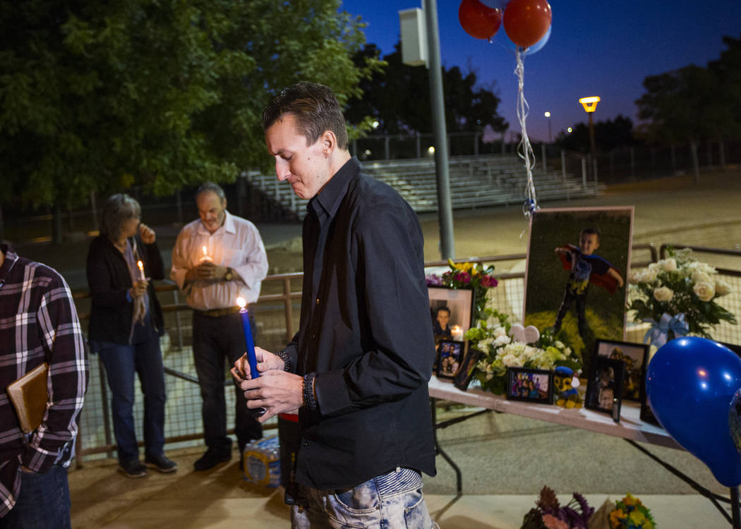 Sean Murray holds a candle while remembering his son, Gavin Murray Palmer, who was lost in a ho ...