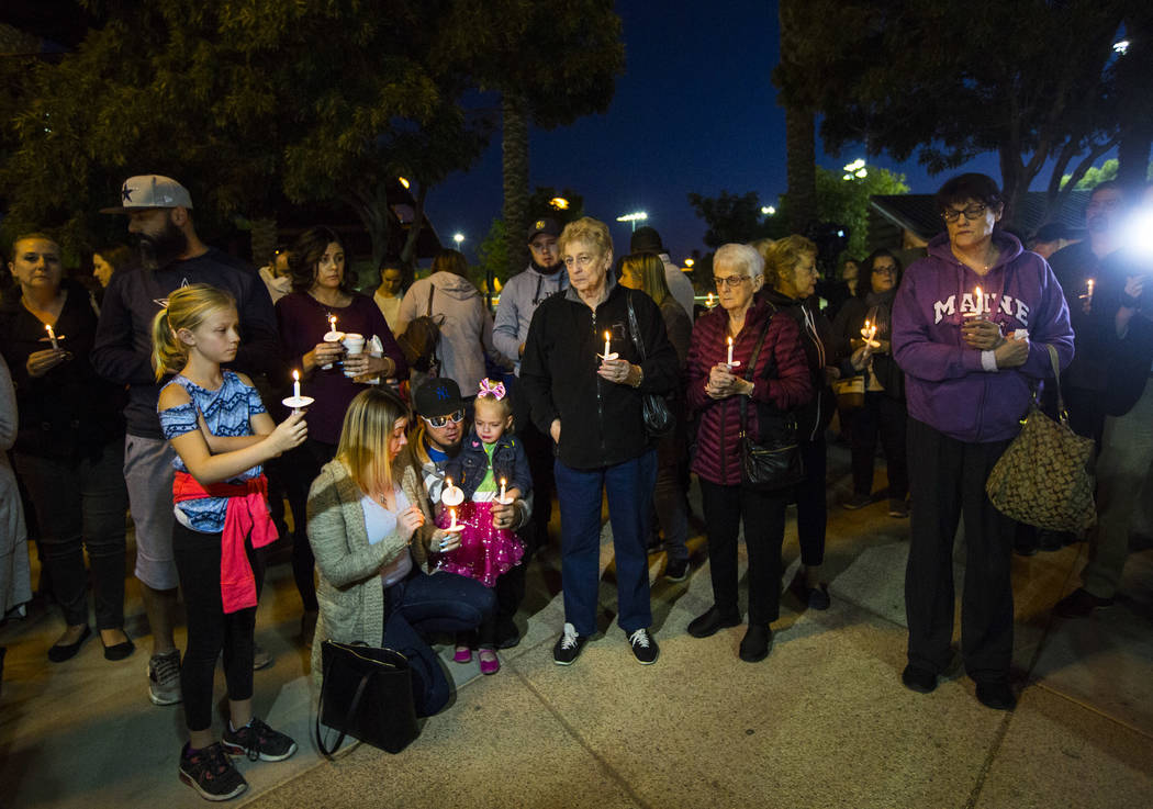 People hold candles in memory of Gavin Murray Palmer, who was lost in a house fire, during a ca ...