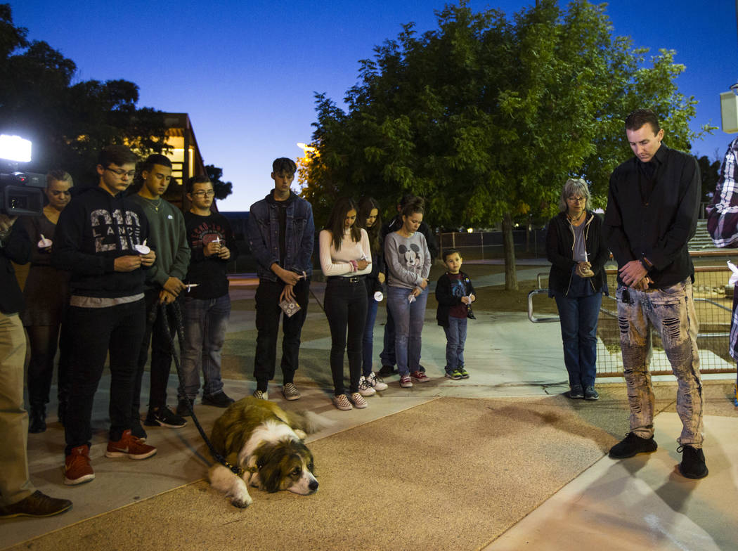 Sean Murray, far right, prays alongside family and friends during a candlelight vigil for his s ...