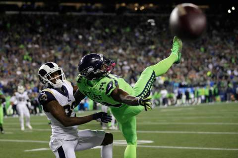 Seattle Seahawks wide receiver DK Metcalf, right, goes down next to Los Angeles Rams cornerback ...