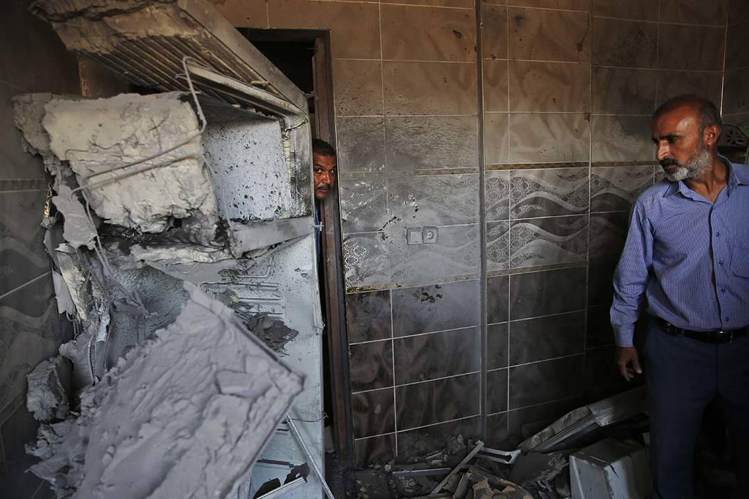 Halil Tokak, right, the neighborhood chief and another resident, inspect the damage on a house, ...