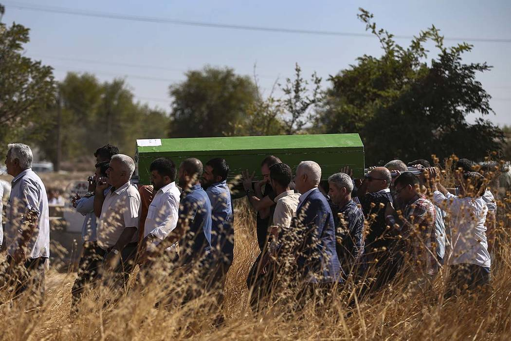 Mourners carry the coffin of Halil Yagmur, 64 killed Friday during mortar shelling from Syria, ...