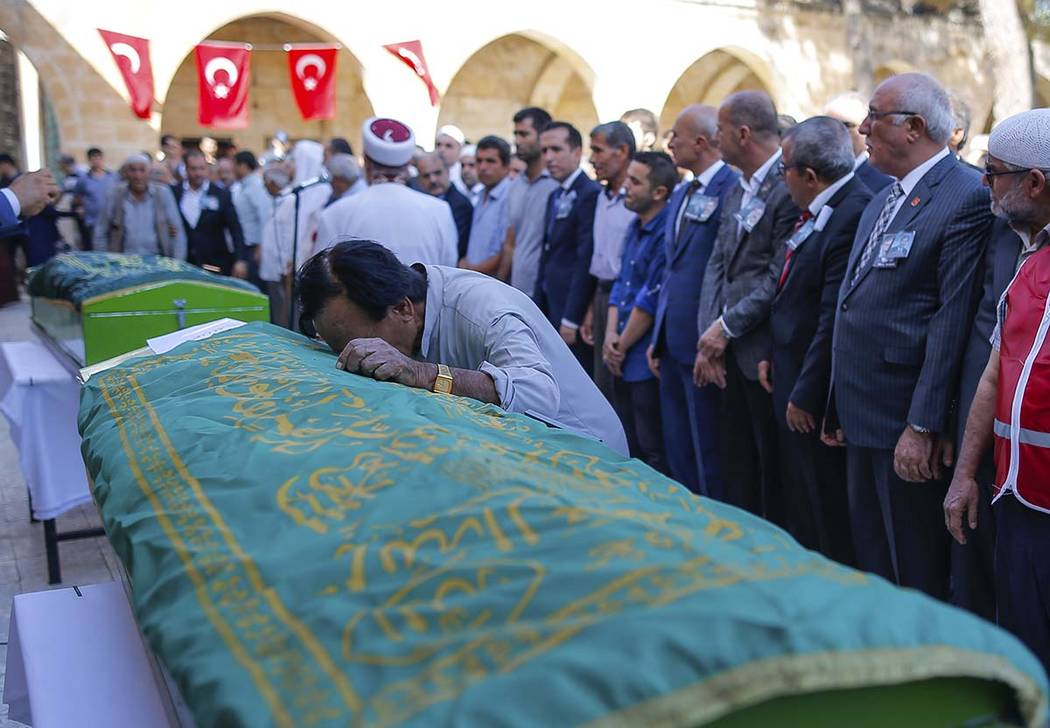 A mourner cries on the coffin of Halil Yagmur, 64, killed Friday during mortar shelling from Sy ...
