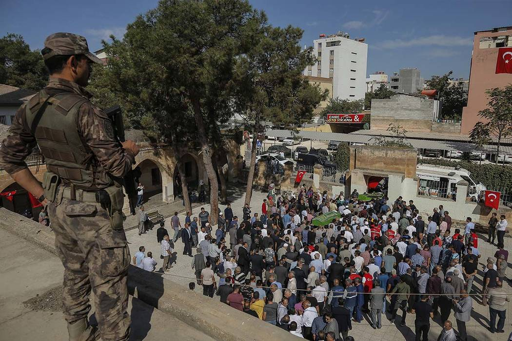 A Turkish soldier watches as mourners carry the coffins of Halil Yagmur, 64 and Muslum Guzel, k ...