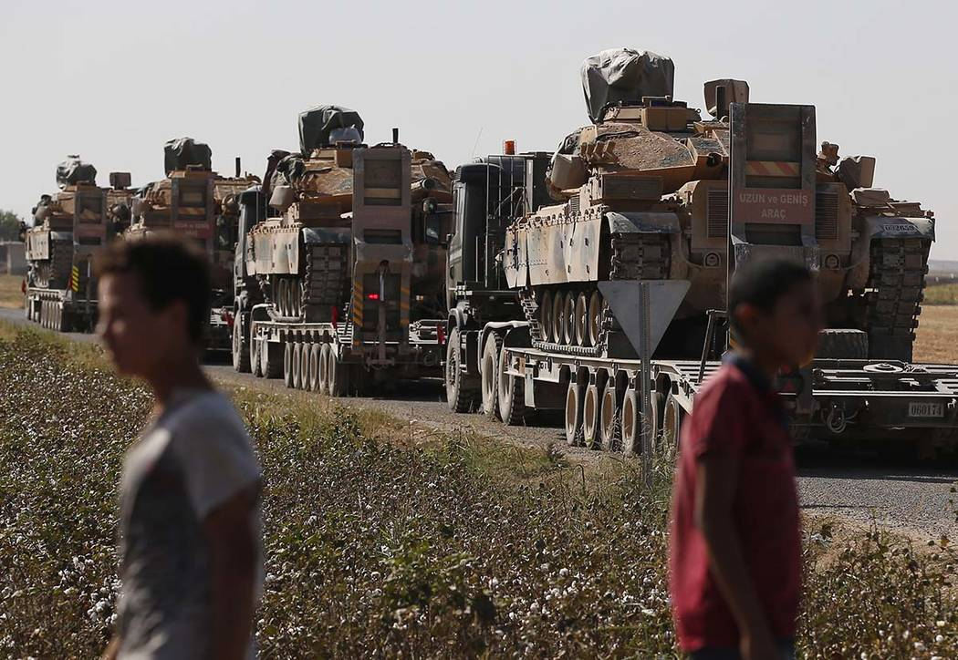 Local residents look on as a convoy of Turkish forces' trucks transporting tanks is driven on a ...