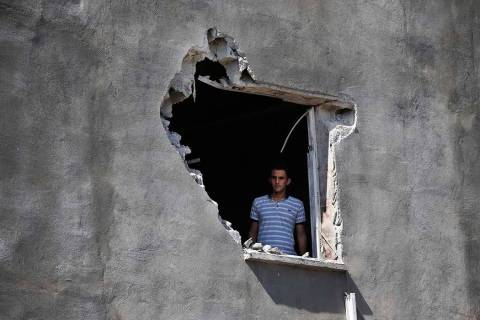 A local resident looks out from a hole on a house that was damaged by a mortar fire from inside ...