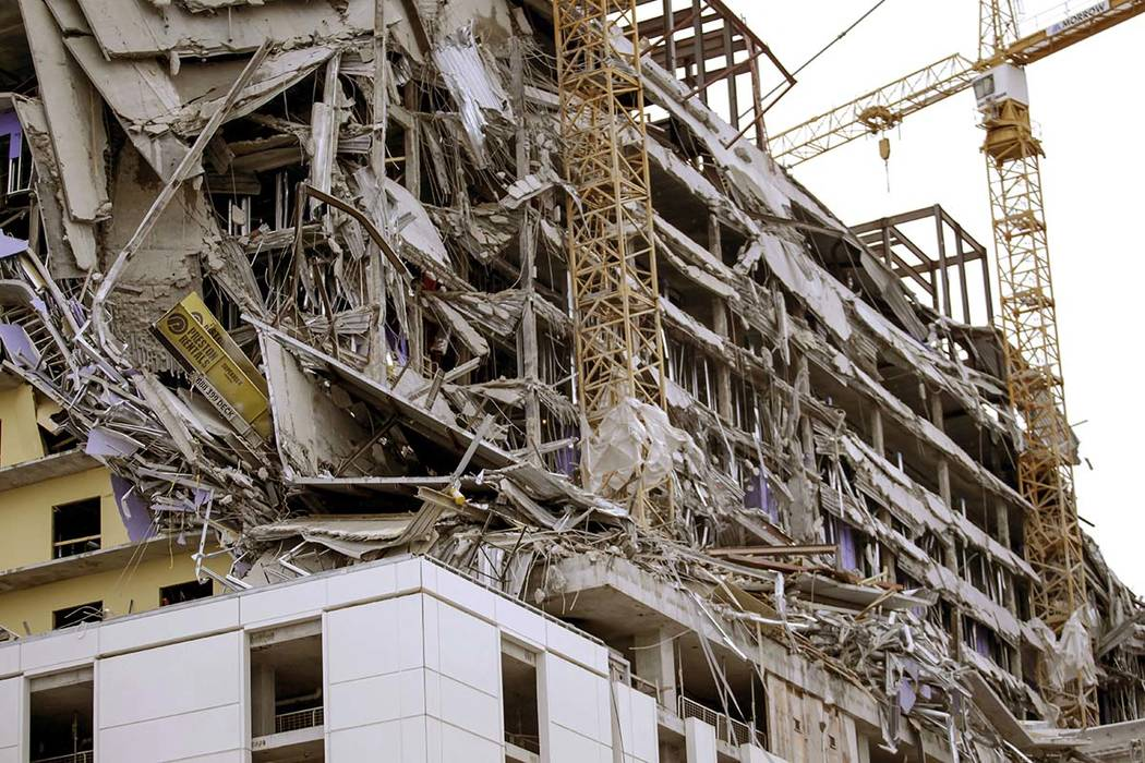 Debris hangs on the side of the building after a large portion of a hotel under construction su ...