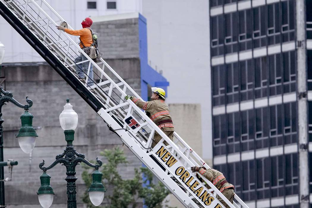 A rescued worker, left, and a firefighter look back at the damaged building after a large porti ...