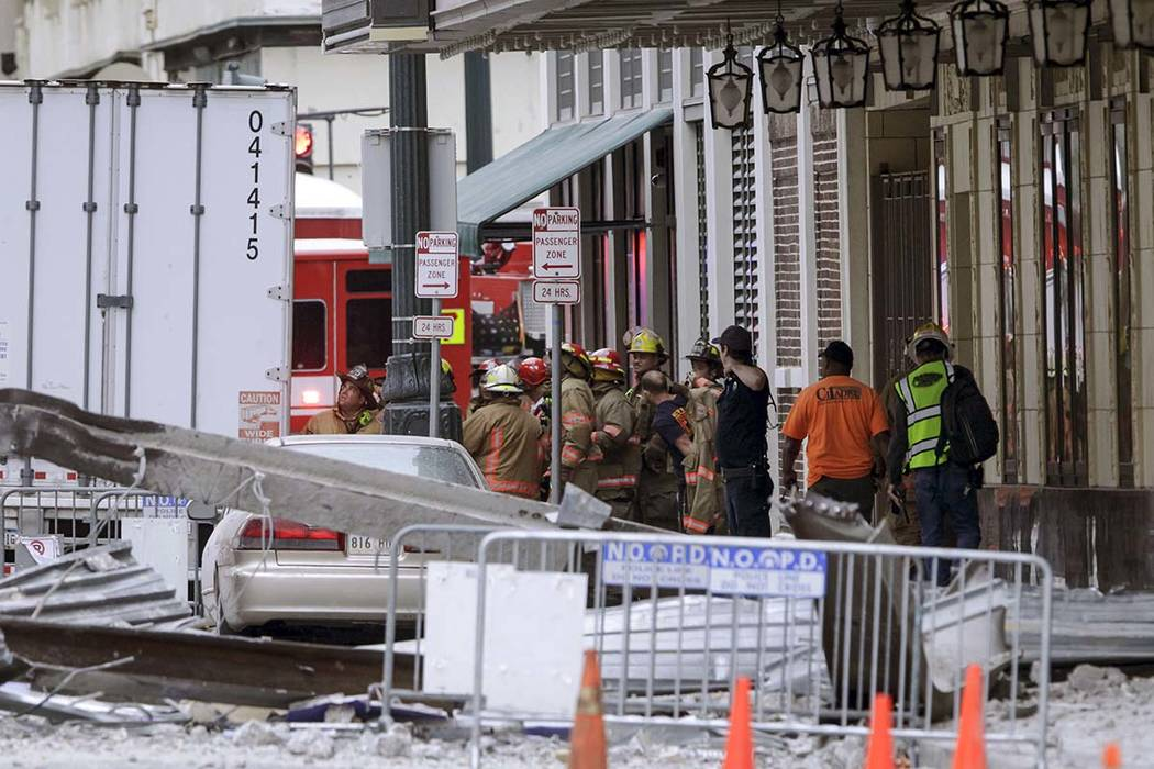 Construction workers are helped by emergency personnel after a large portion of a hotel under c ...
