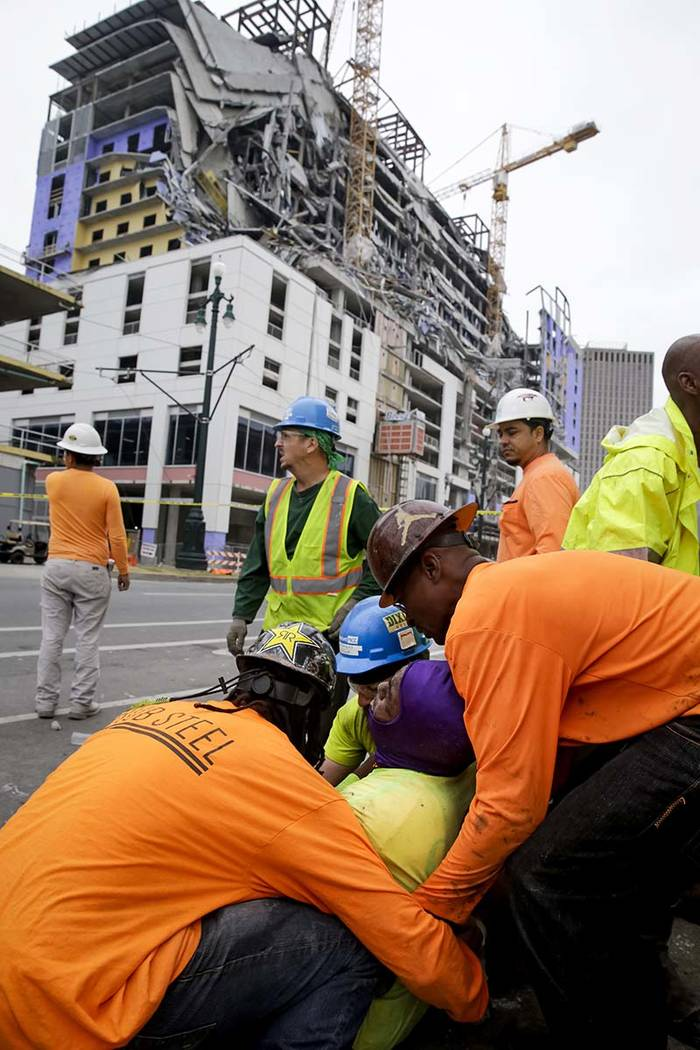 Workers are helped after a large portion of a hotel under construction suddenly collapsed in Ne ...