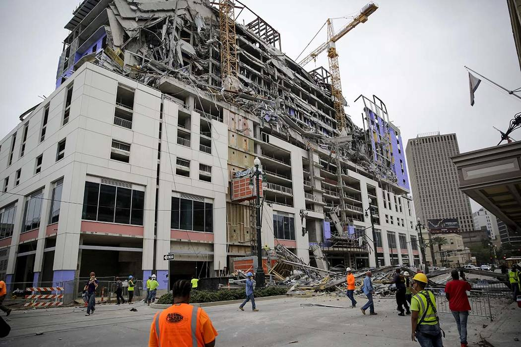Construction workers look on after a large portion of a hotel under construction suddenly colla ...