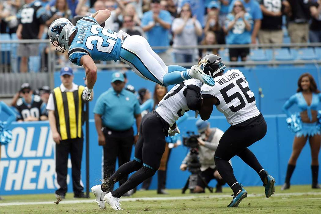 Carolina Panthers running back Christian McCaffrey (22) jumps over Jacksonville Jaguars cornerb ...