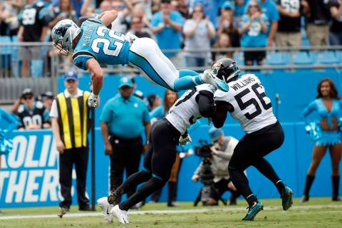 Carolina Panthers running back Christian McCaffrey (22) jumps over Jacksonville Jaguars cornerb ...
