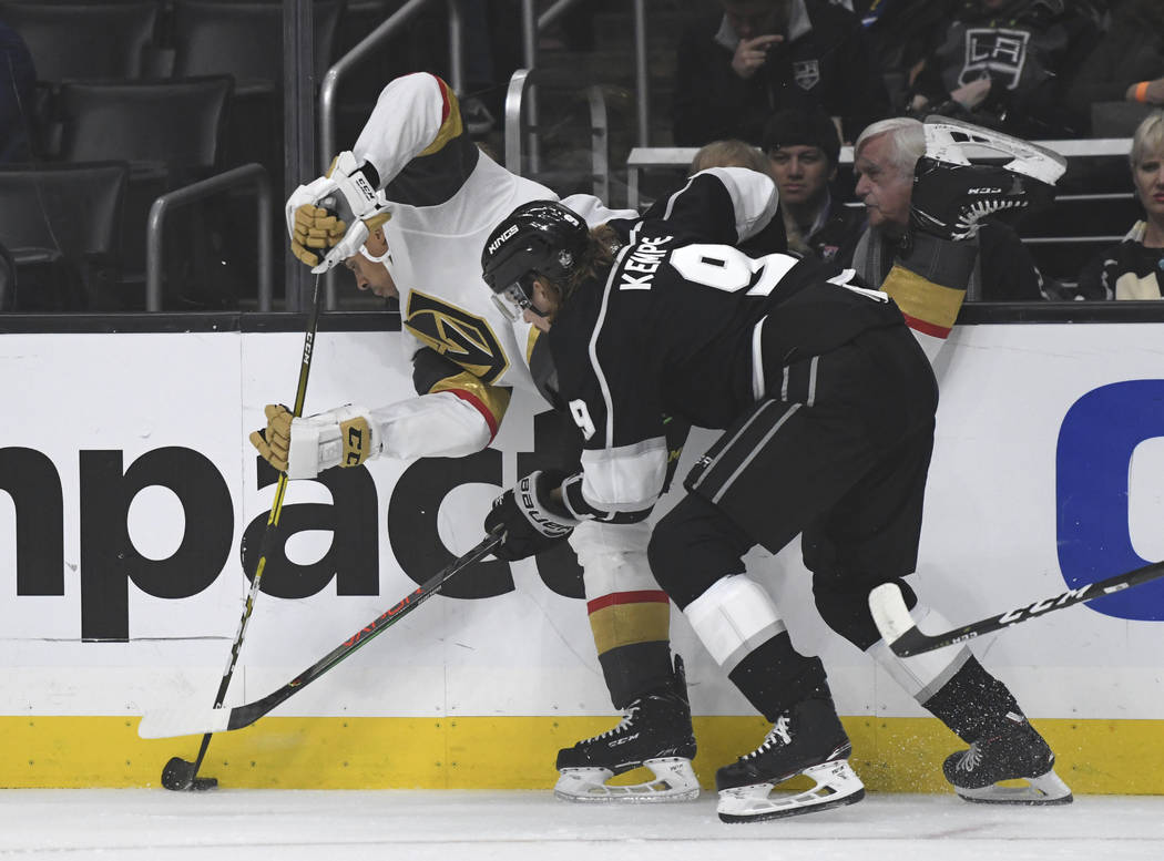 Los Angeles Kings right wing Adrian Kempe, of Sweden, right, checks Vegas Golden Knights right ...