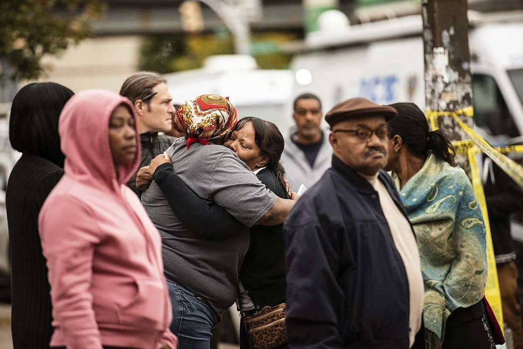 Two people embrace at the scene of a shooting in the Brooklyn borough of New York on Saturday, ...