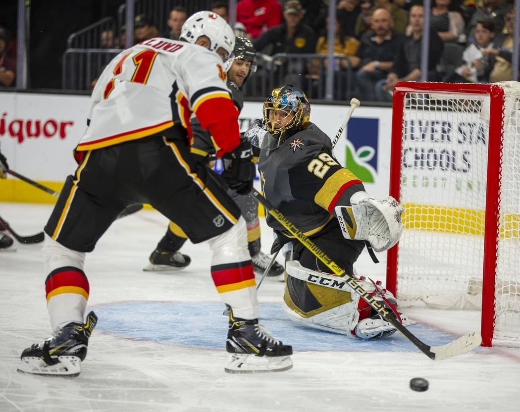 Vegas Golden Knights goaltender Marc-Andre Fleury (29, right) deflects a shot by Calgary Flames ...