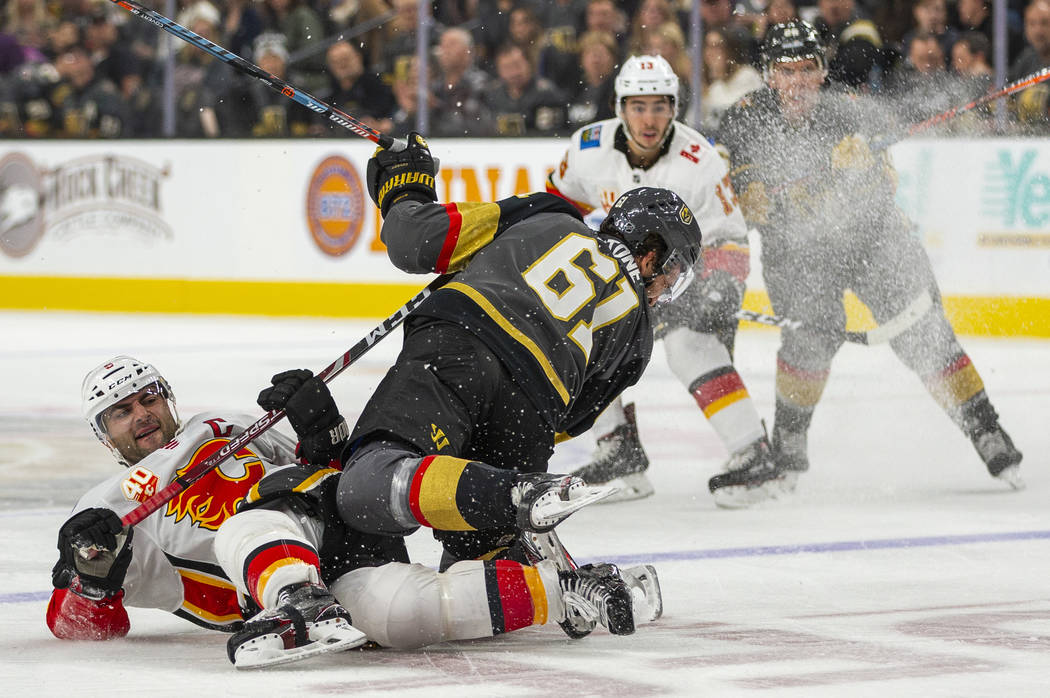 Calgary Flames defenseman Mark Giordano (5, left) takes out Vegas Golden Knights right wing Mar ...