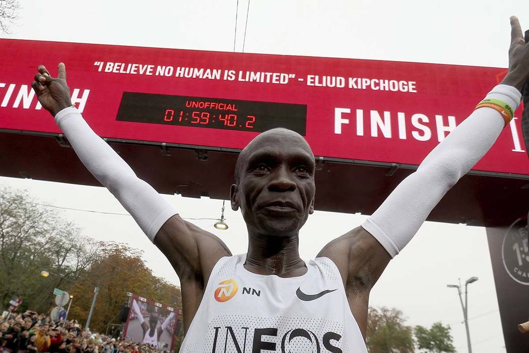 Marathon runner Eliud Kipchoge from Kenya celebrates under the clock after crossing the finish ...
