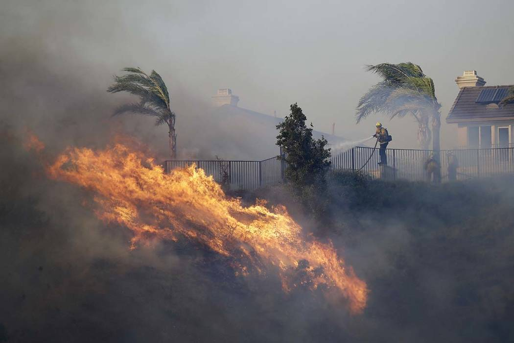 A firefighter sprays water in front of an advancing wildfire Friday, Oct. 11, 2019, in Porter R ...