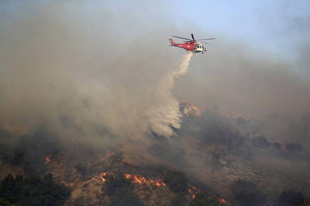 A helicopter drops water onto an advancing wildfire Friday, Oct. 11, 2019, in Porter Ranch, Cal ...