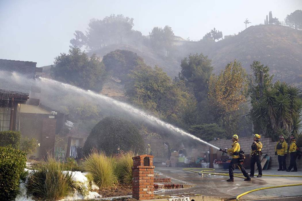Firefighters hose down the roof of a house damaged by a wildfire Friday, Oct. 11, 2019, in Port ...