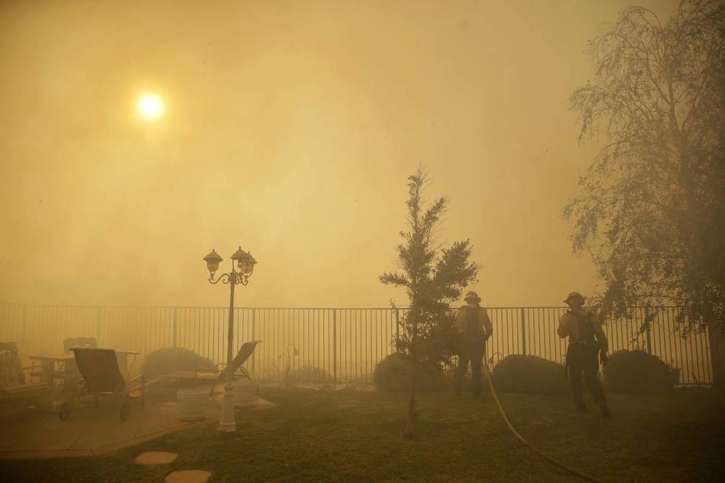 Firefighters make a stand on an advancing wildfire as smoke fills the air Friday, Oct. 11, 2019 ...