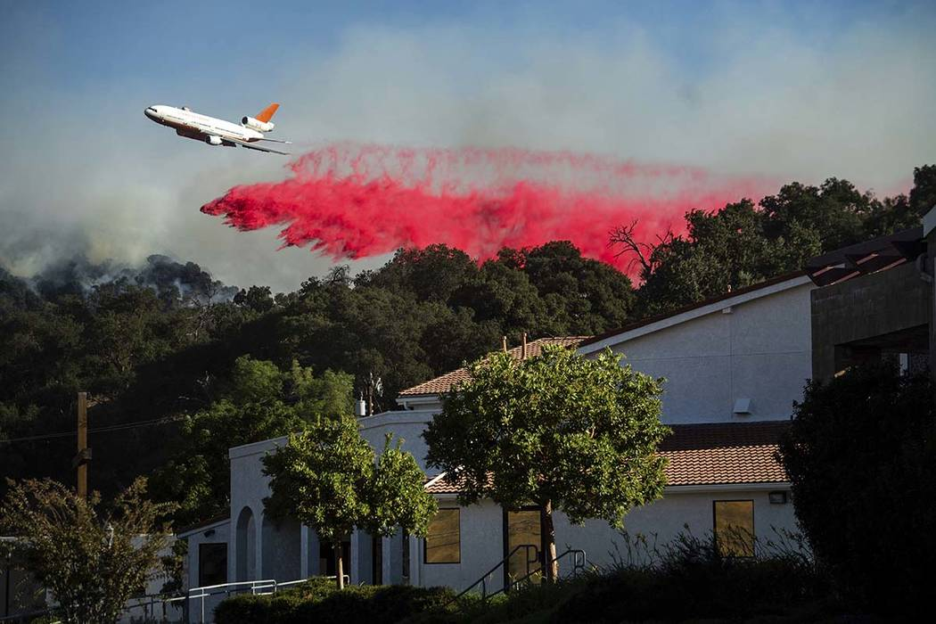 An air tanker drops retardant behind the Newhall Church of the Nazarene while battling the Sadd ...