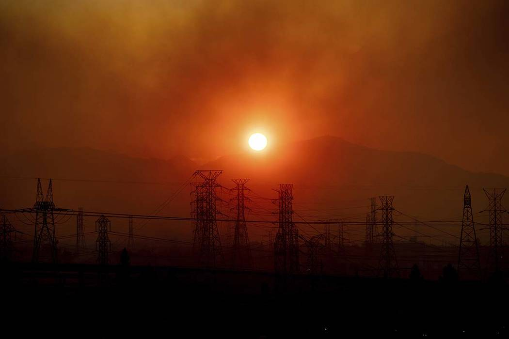 Smoke from the Saddleridge Fire hangs above power lines as the sun rises in Newhall, Calif., on ...