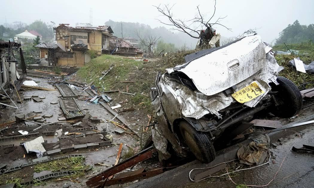 A damaged car lies on the ground following a strong wind in Ichihara, Chiba, near Tokyo Saturda ...