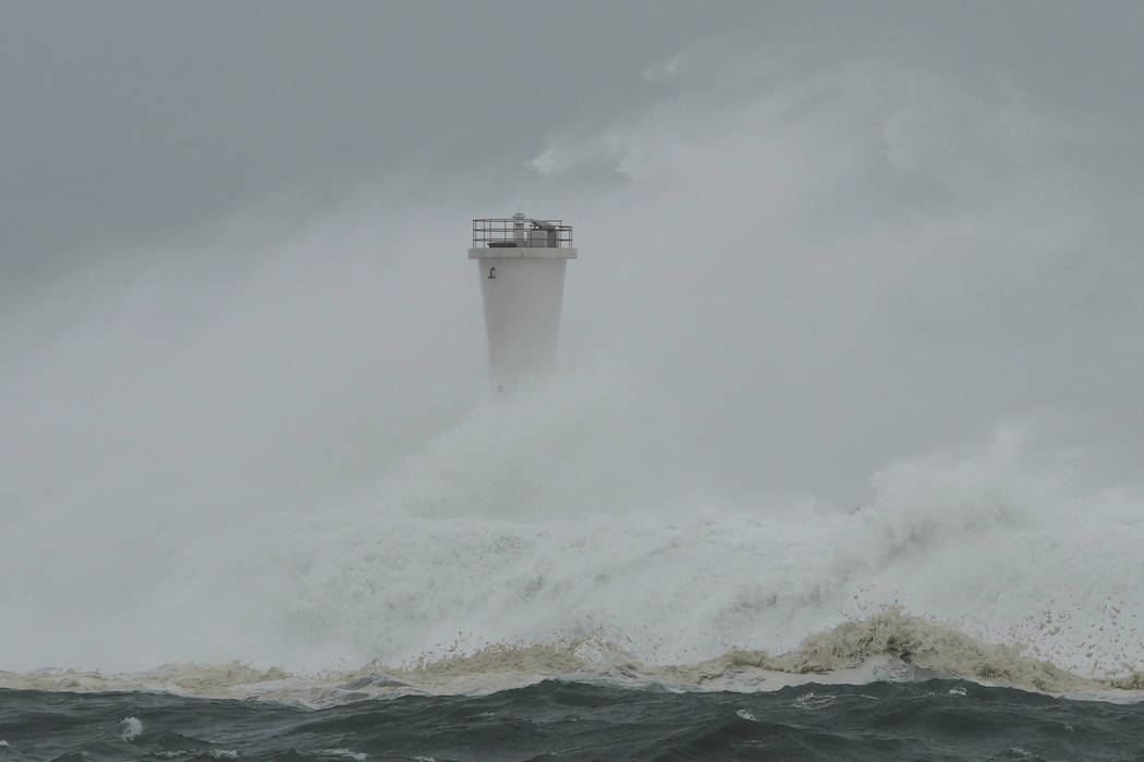 Surging waves hit against the breakwater and a lighthouse as Typhoon Hagibis approaches at a po ...