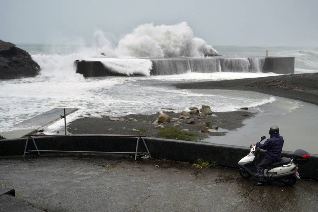 A man on a scooter watches as surging waves hit against the breakwater as Typhoon Hagibis appro ...