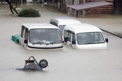 Cars sit submerged in water in the residential area hit by Typhoon Hagibis, in Ise, central Jap ...
