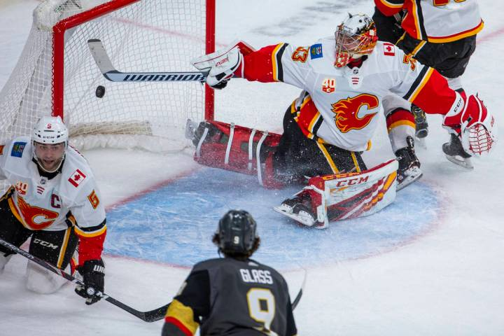 Calgary Flames goaltender David Rittich (33, top) is unable to stop a shot into the net by Vega ...