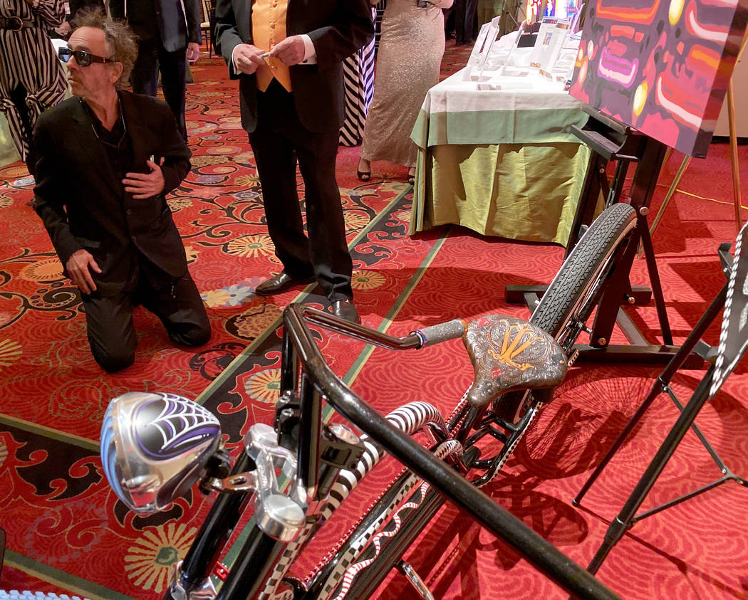 Tim Burton signs a custom bicycle by Brad Marlon up for auction during cocktail hour at The Neo ...