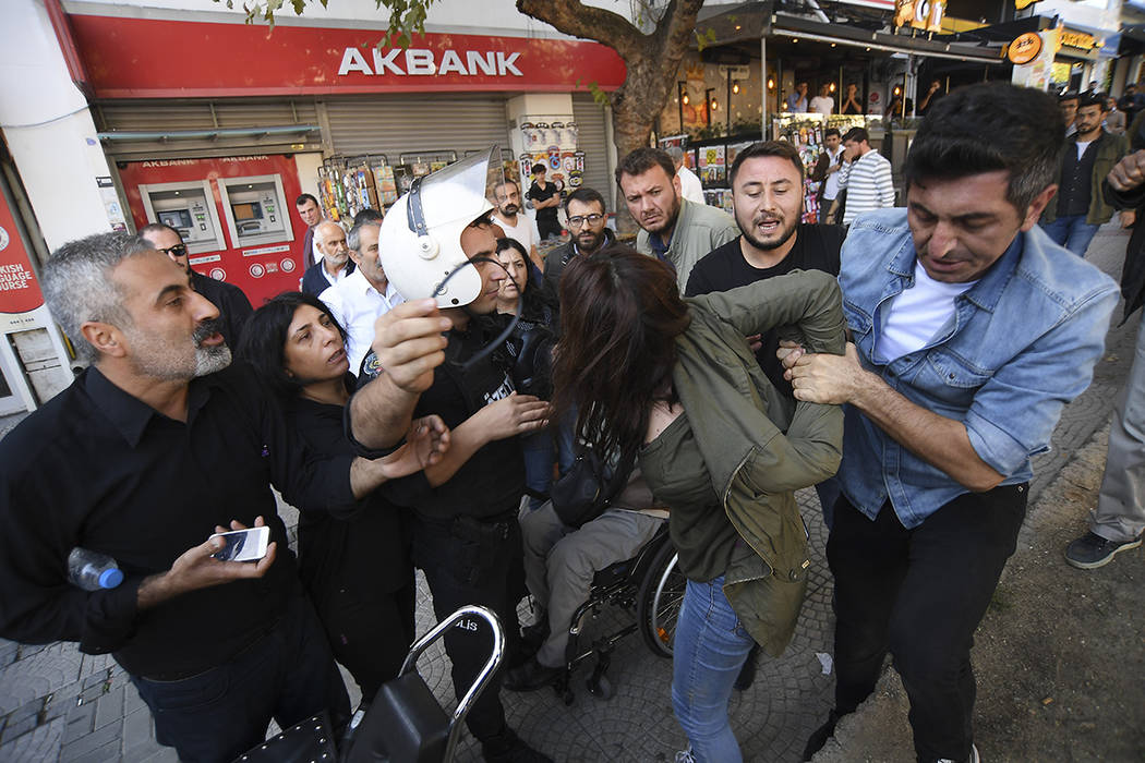 Security officials detain a pro-Kurdish party member who is protesting against Turkey's militar ...