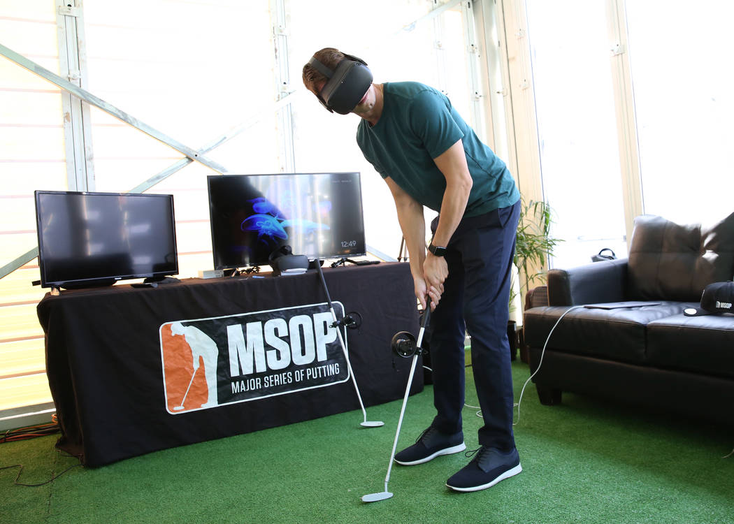 Robert Holzhauer, director of operation at Pro Putt, demonstrates how virtual reality putting i ...