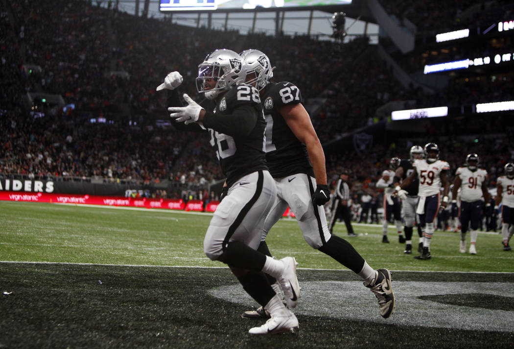 Oakland Raiders running back Josh Jacobs (28) celebrates his touchdown with tight end Foster Mo ...