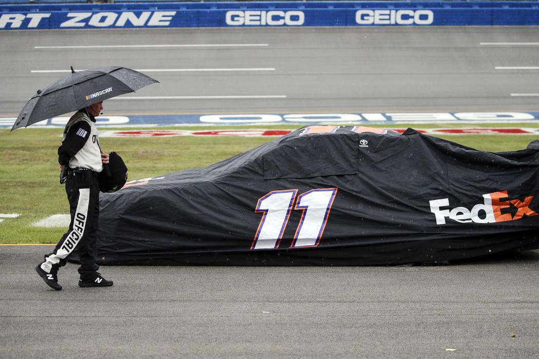 An official walks by the car of Denny Hamlin (11) car during a rain delay in a NASCAR Cup Serie ...