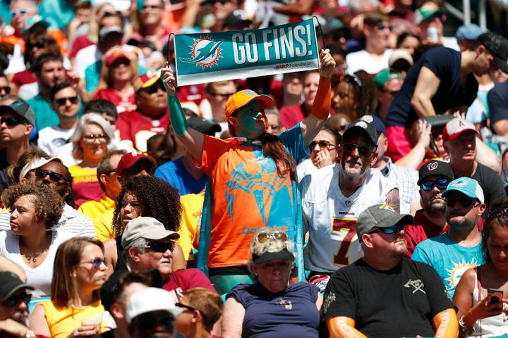 Miami Dolphins fans cheer the team, during the first half at an NFL football game against the W ...