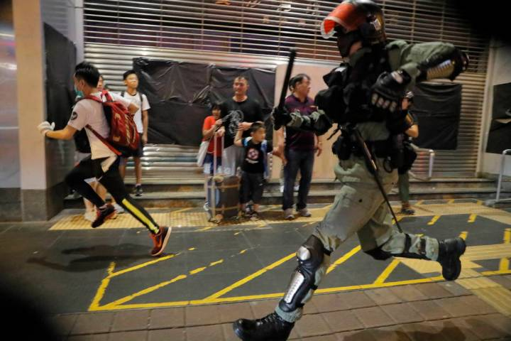 Police chase a protester in Hong Kong, Sunday, Oct.13, 2019. Protesters changed tactics and pop ...