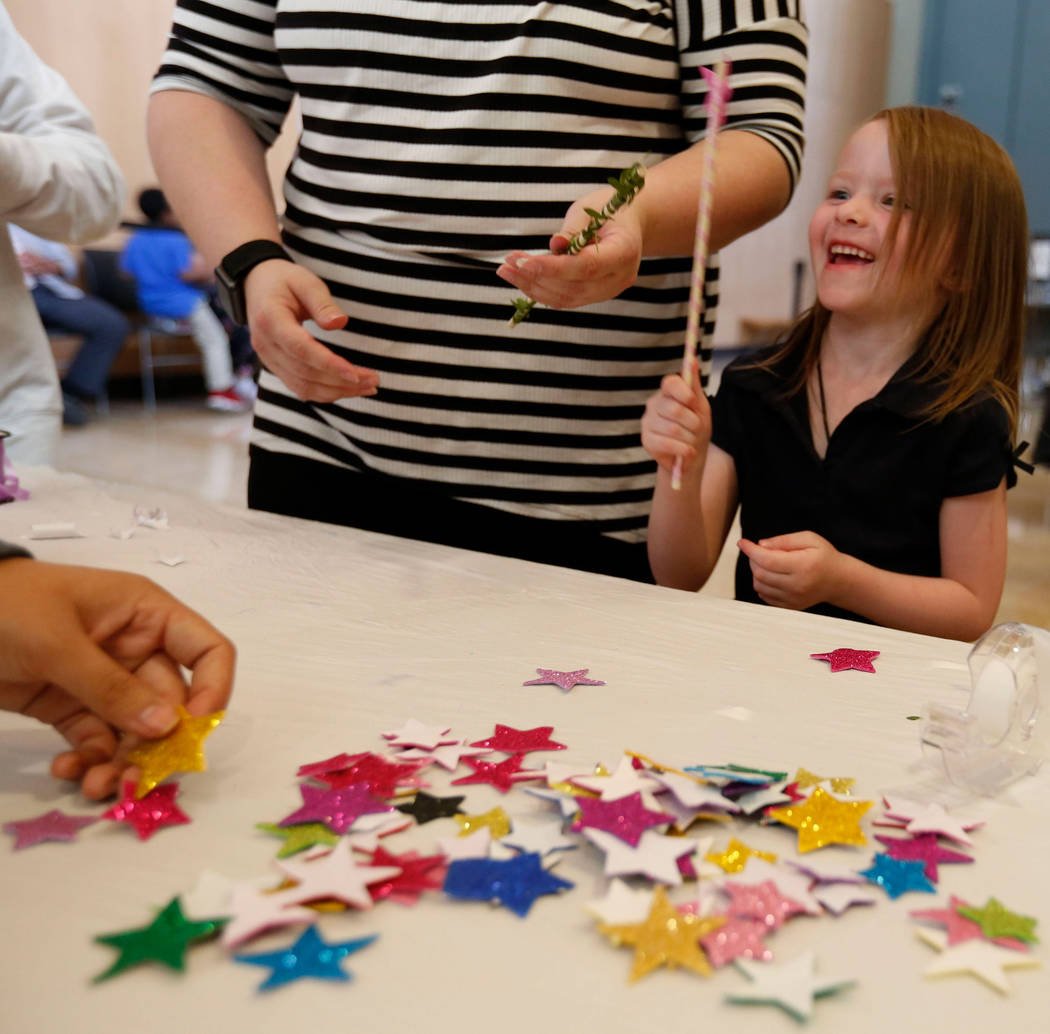 Haylee Applegate, 5, of Las Vegas makes a wand with her mother Ashley Brookins during Mystic Fa ...