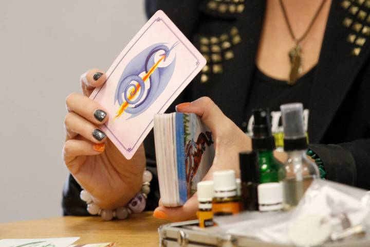 Local psychic Nicole Borghi shows a card during her angel card reading session with her client ...